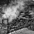 Stock Photo: Black and white mountain house roof with smoking chimney