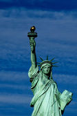 Statue of liberty close up vertical isolated in blue cloudy background — Stock Photo