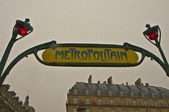 Paris Metro Metropolitain Sign near Louvre under snow flakes — Stock Photo
