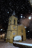 A church while snowing in the winter night — Stok fotoğraf