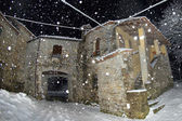 An old stone house while snowing in the winter night — Stock Photo