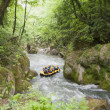 Teamwork of Rafting on a creek in yellow boat — Stock Photo
