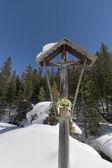 Holz geschnitzte christus im schnee-hintergrund — Stockfoto
