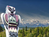 A totem wood pole in mountain background — Stockfoto