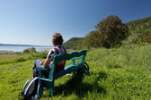 Woman looking the sea while sitting on a bench — Stock Photo