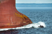 Dolphin jumping over ship prow — Stock Photo