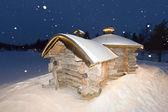Wooden hut in snow background — Zdjęcie stockowe