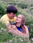 Young couple on flower meadow — Stock Photo