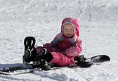 Toddler girl sitting on snowboard — Stock Photo