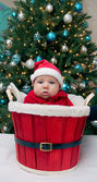Baby boy in Santa hat in the red basket — Zdjęcie stockowe