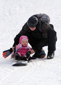 Father and daughter sliding on snowboard — Stock Photo