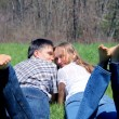 Happy young couple having rest on the meadow — Stock Photo