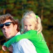 Father holding his daughter on shoulders — Stock Photo #42158751