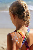 Girl on the beach with sunscreen lotion — Stock Photo
