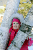 Girl looks out tree trunk — Stock Photo