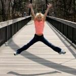 Girl jumping on the bridge — Stock Photo
