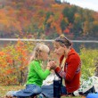 Mother and her daughter drinking tea in fall park — Stock Photo #42686645