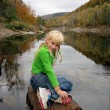 Girl sitting on the stone near the river — Foto de Stock