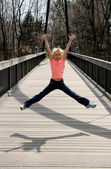 Girl jumping on the bridge — Stock Photo