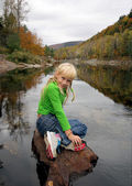 Girl sitting on the stone near the river — Stock Photo