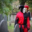 Постер, плакат: Scary Joker with skeleton face looking at the headstone