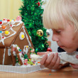 Girl is decorating the gingerbread house — Stock Photo #42894745