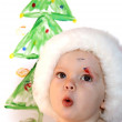 Cute toddler in Santa hat with finger painting Christmas tree — Stock Photo