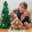 Happy mother and daughter are decorating gingerbread house — Stock Photo
