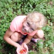 Portrait of a beautiful little girl with the handful of the wild strawberries — Stock Photo