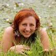 Beautiful redhead woman laying in the grass near the lake — Stock Photo #42894997