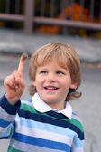Funny little curious boy with the bur on his finger — Stock Photo