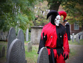 Scary Joker with skeleton face looking at the headstone — Stock Photo