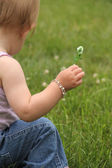 Little child's hand holding out a clover flower — Stock Photo