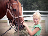 Cute little girl petting the horse — Foto Stock