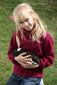 Little girl plays with Guinea pig outside — Stock Photo