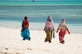 Three women walking on the beach — Stock Photo