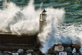 Lighthouse under the power of the waves — Stock Photo