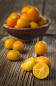Tasty kumquats on a wooden top — Stock Photo