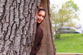 Young girl peaking from a hollow tree — Stock Photo