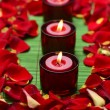 Candles with red rose petals - Stock Photo