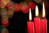 Three red candles and bokeh of colored balls — Stock Photo