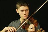 Man met een viool op een zwarte achtergrond — Stockfoto