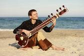 Muž hrát sitar blízko moře — Stock fotografie