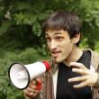 Evil guy with megaphone makes announcement — Stock Photo #24881777