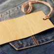 Jeans with blank paper label on a string — Stock Photo