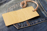 Jeans with blank paper label on a string — Zdjęcie stockowe