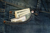 Condom and three dollars in the pocket jeans — Stock Photo