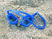 Blue swimming goggles for diving underwater lying on the sand — Stock Photo