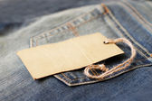 Jeans with blank paper price tag — Stock Photo
