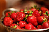 Lots of strawberries in colander — Stock Photo